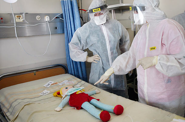 Israeli nurses stand over a doll, representing an injured baby, during a drill simulating a biological attack at Chaim Sheba Medical Center near Tel Aviv.