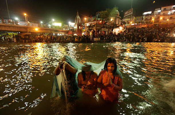 A family offers prayers while wading in the Ganges River on the first day of the Kumbh Mela, or the pitcher festival, in Haridwar, India.