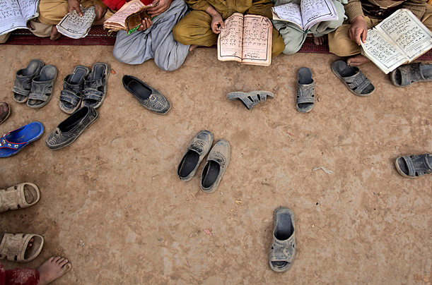 Afghan refugee boys and girls, holding copies of the Quran, Islam's Holy book, are seen outside a house in a poor neighborhood of Rawalpindi, Pakistan.