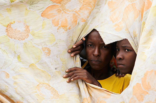 Haitians look through a hole in their makeshift home in Port-au-Prince, Haiti.