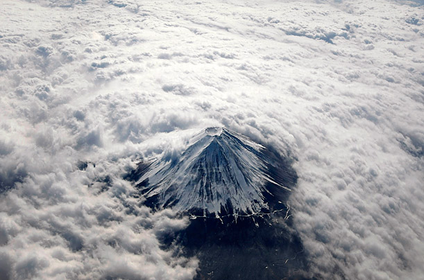 Japan's Mount Fuji is seen from above, covered with snow and surrounded by clouds.