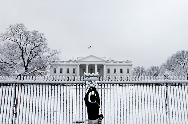 A photographer takes a picture of the North Grounds of the White House in Washington D.C. after fresh snowfall.
