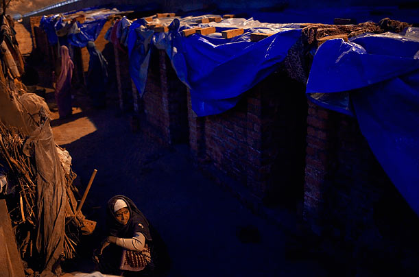 An Indian woman prepares food for dinner at a makeshift home in New Delhi, India.