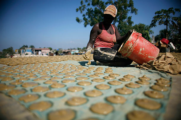 A resident prepares mud cakes at the zone of Cite-Soleil in Port-au-Prince, Haiti. Struggles in aid distribution and the skyrocketing cost of food has left such cakes a dietary staple for many families.
