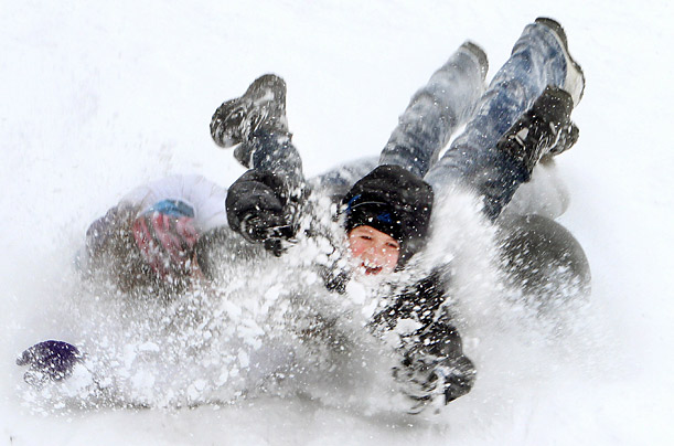 Mason Saegert flies off an inner tube while sledding with his sister Megan Saegert and Kristen Bissett in Amherst, Ohio.