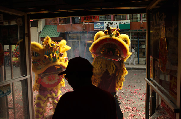 A silhouetted  man looks on as people perform a Lion dance during celebrations of the Chinese New Year at Chinatown neighborhood in Panama City, Monday, Feb. 15, 2010. China celebrates the Year of the Tiger beginning Feb. 14 and