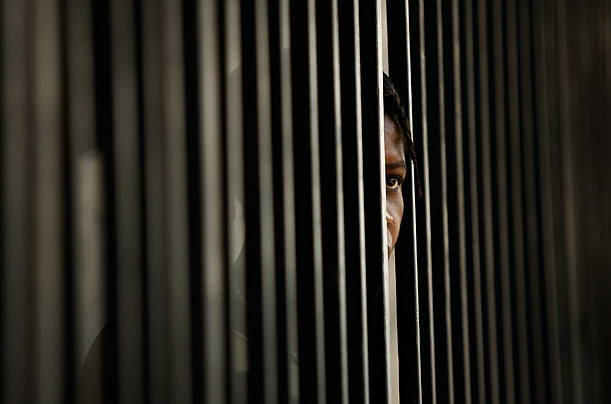 A woman peers out of the fence circling the internally displaced persons camp on the grounds of the Primature, the prime minister's offices in Port-au-Prince, Haiti.