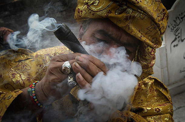 A Pakistani devotee smokes during the annual festival of the 14th century Sufi Saint Mian Mir in Lahore.