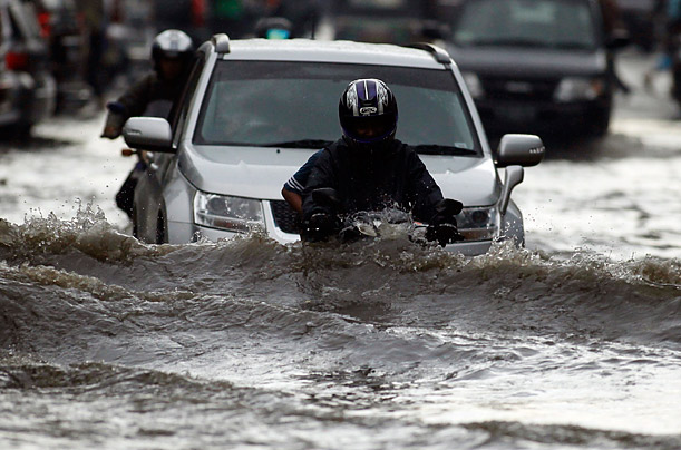 A motorcyclist rides through a flooded street in Jakarta after heavy rains.