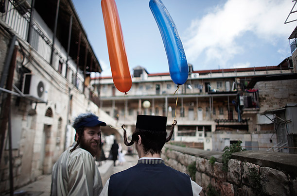 Jewish orthodox men walk in the street of the conservative Mea Shearim neighborhood in Jerusalem during the commemoration of the Jewish feast of Purim.