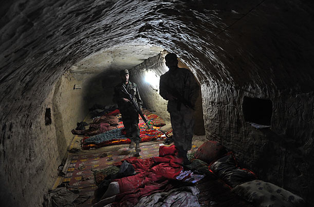 Pakistani soldiers leave a cave complex, located in Damadola, Pakistan, that served as a key Taliban and Al-Qaeda headquarters.