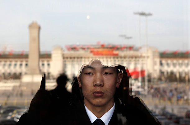 A Chinese security guard in the Great Hall of the People in Beijing, China is seen standing behind glass reflecting Tiananmen Square.