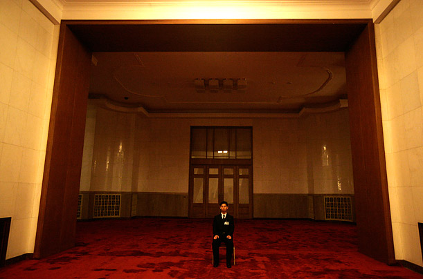 A security guard sits in an archway at the Great Hall of the People during a meeting of the National People's Congress.