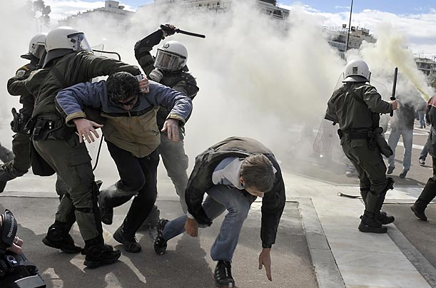 Demonstrators tangle with riot police in front of the Greek parliament in Athens after the country froze pensions and raised taxes to cut spending, part of an effort to persuade the European Union that it can avoid bankruptcy.