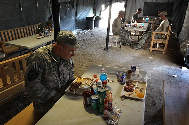 Catholic chaplain Cpt. Carl Subler stares at his breakfast at an American combat outpost in Kandahar province, Afghanistan. Chaplain Subler travels throughout Afghanistan, providing spiritual support to thousands of soldiers.