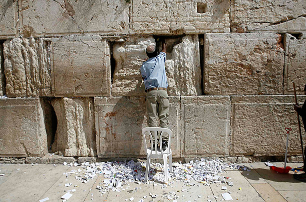 A worker removes notes from the cracks of the Western Wall, Judaism's holiest prayer site, in Jerusalem's Old City March 17, 2010. Workers cleaned out the cracks and made room for more paper notes that Jews believe are notes to God, ahead of the hol