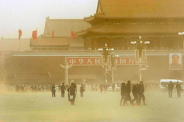 Locals walk in the sandstorm at Tiananmen Square in Beijing, China. Beijing woke up to orange-tinted skies Saturday as the strongest sandstorm so far this year hit the country's north.