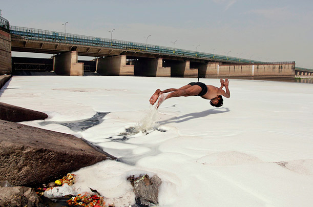Shakeel dives into a polluted section of the River Yamuna to scavenge for ornaments and coins left by Hindu rituals at the river bank,