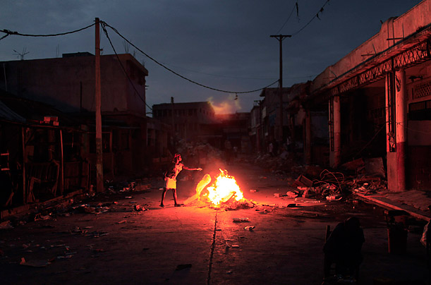A woman throws paper onto a fire burning in the middle of a street in Port-au-Prince, Haiti.