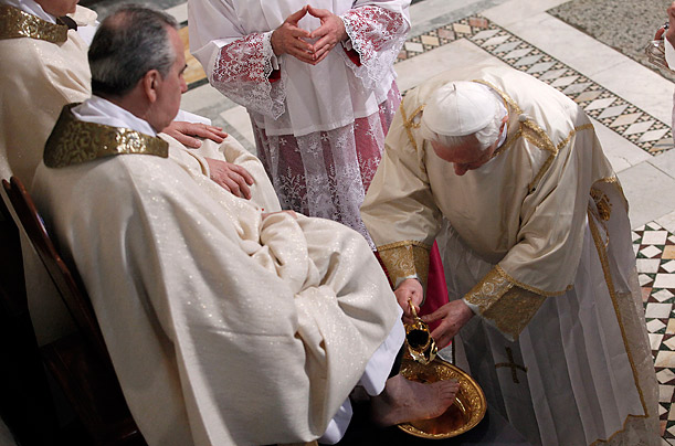 Pope Benedict XVI washes the feet of a layman at a Cathedral in Rome, part of a ritual symbolizing humility observed on Holy Thursday.
