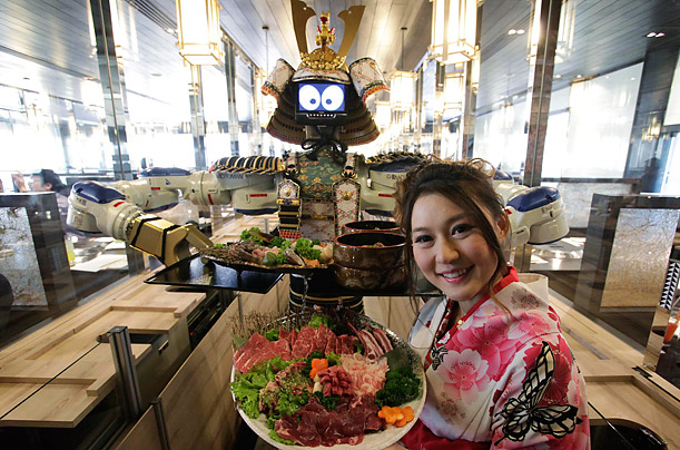 Lapassarada Thanaphant poses with a robot waiter at the opening ceremony of her restaurant, Hajime, in Bangkok, Thailand.