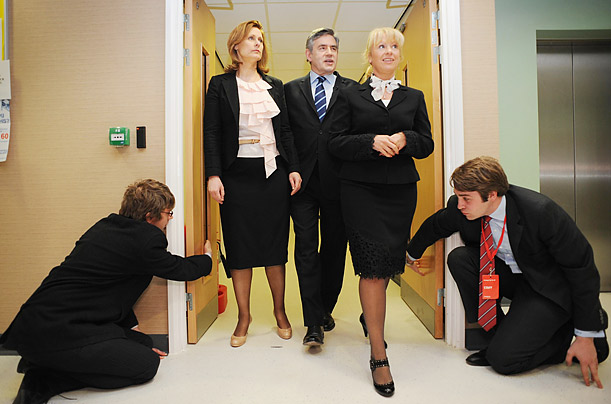 Two aides crouch down to open doors for British Prime Minister Gordon Brown, center, his wife Sarah, left, and Sam Prince, Managing Director of the Leeds Community Health Care, during a visit to a health center in Yeadon, England.
