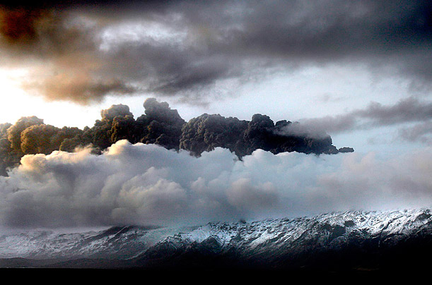 Smoke and steam hang over the volcano under the Eyjafjallajokull glacier in Iceland, which has erupted floodwaters and canceling flights across Europe.