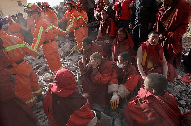 Ethnic Tibetan monks sit near rescuers at the site of a collapsed dormitory building at a local school after a 6.9-magnitude earthquake hit Jiegu Town of Yushu County, strong earthquake in China