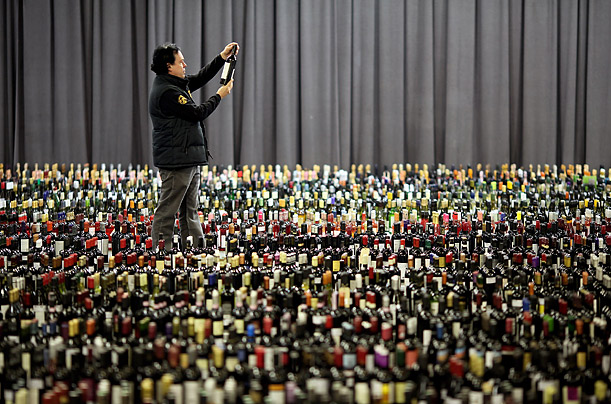 A judge selects one of the over 10,000 bottles of wine for tasting during the International Wine Challenge in London.  Bottles are shipped from across the globe to be considered.