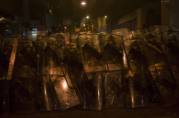 Thai army soldiers protect themselves behind riot shields after a series of explosions on Silom road in the financial district of central Bangkok.