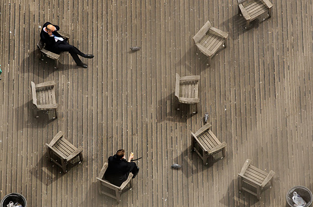 Londoners relax in chairs on an early summer morning.