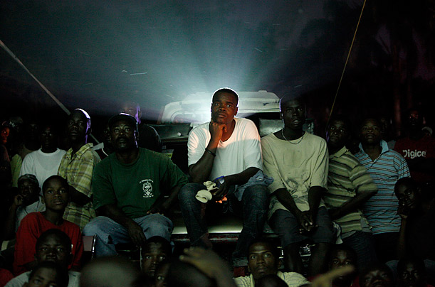 People gather to watch a soccer game between Haiti and Argentina, played in Argentina, projected on a video screen on a street in Port au Prince.