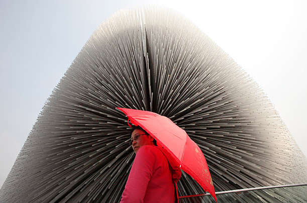 A visitor stands outside the United Kingdom Pavilion at the Shanghai World Expo in China.