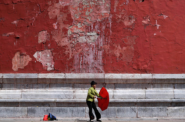 A Chinese woman manages to hold on to her umbrella against a strong wind while visiting the Forbidden City in Beijing, China.