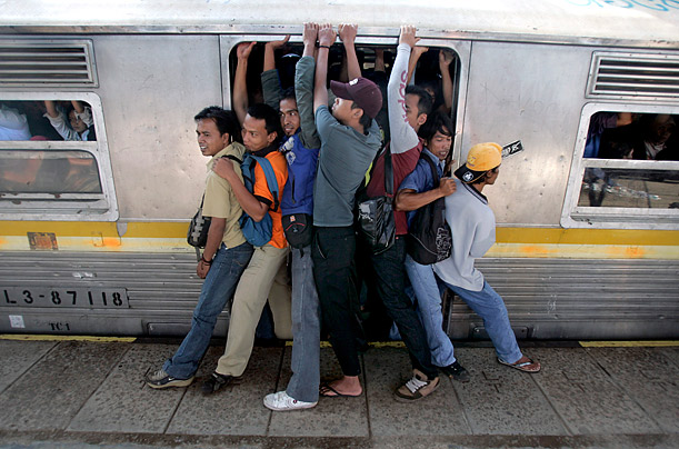 Indonesian men struggle to board a packed commuter train at a station in Jakarta, Indonesia.