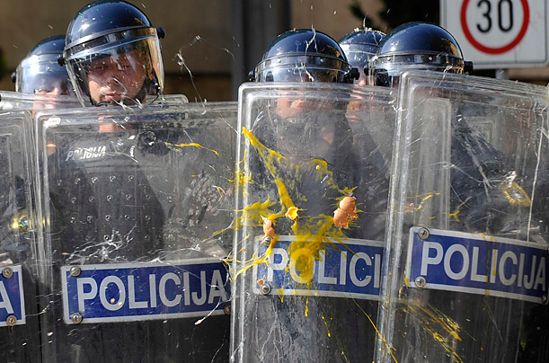 Slovenian police shield themselves from eggs, hurled by students protesting government proposed restrictions on part-time labor.