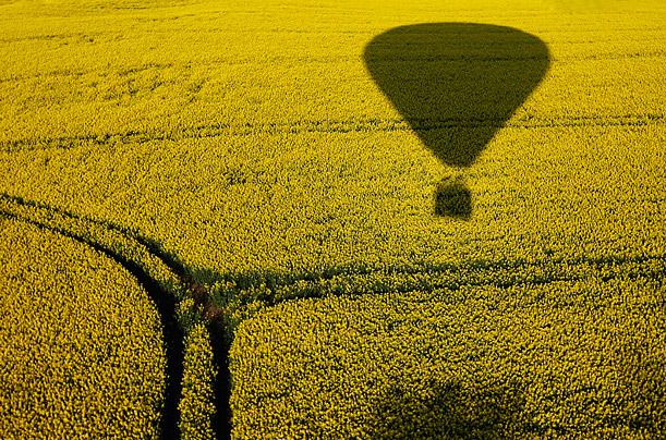 The silhouette of a hot-air balloon hovers over a field near Jasdorf, Germany.