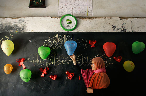 A student gives final touches to classroom decorations for a National Teacher's Day celebration in Herat, Afghanistan.