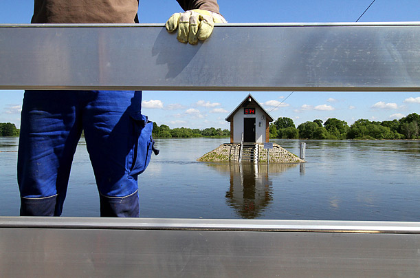 A man works on building a wall to hold back the flooding Oder River in the Polish-German Border town of Ratzdorf.  Floods from Poland arrived sooner then expected due to sudden torrential rainfall.