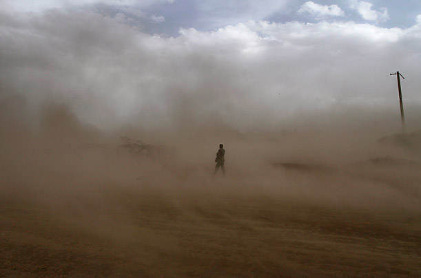 An Afghan man walks through a dust storm in Kabul.  Dust storms are common throughout the region, causing adverse effects on crops and health problems with residents.