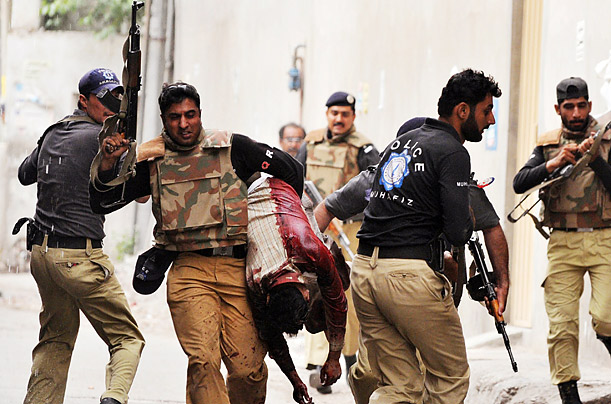 A Pakistani commando carries an injured, bloodied worshiper to safety after gunmen attacked two minority sect Ahmedi mosques in Lahore, Pakistan.