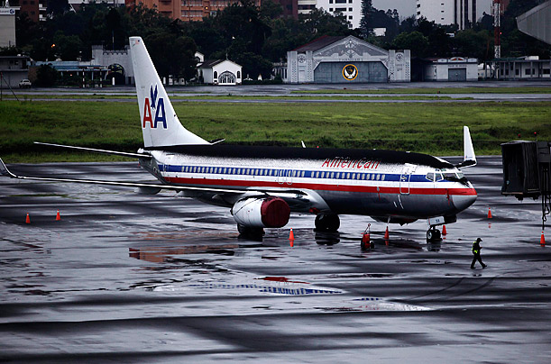 An American Airlines jet sits covered with ash from the eruption of the Pacaya Volcano on the runway at the International airport in Guatemala City.