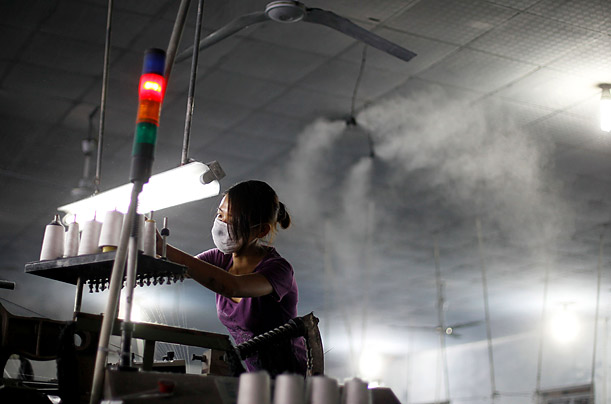 An employee works on a threading machine at the Su Yin Denim Co. Ltd. in Jiangyin, Jiangsu province.  The Chinese textile industry produces clothing for many of the popular brands throughout the U.S. and Europe.