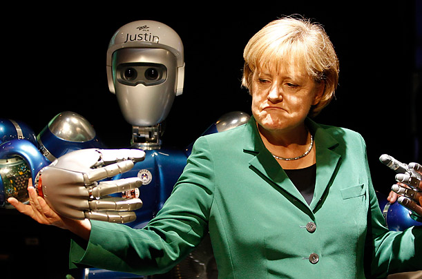German Chancellor Angela Merkel makes a face as she investigates a robot called 