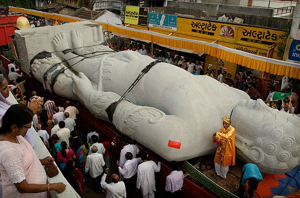 A crowd gathers to watch a 41 foot tall statue of Jain sage Lord Bahubali roll through their village. The statue was carved out of a single block of granite and has traveled nearly 125 miles from Ahmadabad to Songadh, India.