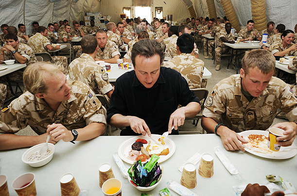 Britain's Prime Minister David Cameron, center, eats breakfast with British forces at Camp Bastion in Helmand Province, Afghanistan.
