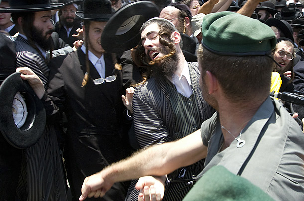 An Israeli police officer clashes with an Ultra-Orthodox Jewish man during a protest over a construction site that is said to be located on a Jewish burial ground.
