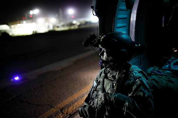 An army seargent takes a moment while transporting a shooting victim on a Blackhawk helicopter.