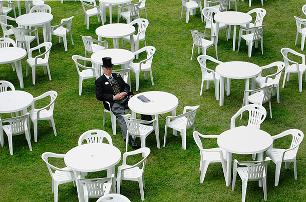 A racegoer sits alone before the start of the fourth day of racing at the Royal Ascot in southern England.
