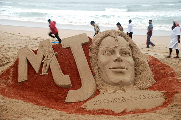 People walk past a sand sculpture of Michael Jackson at the Bay of Bengal coast, in Puri, India created to mark the first anniversary of his death.